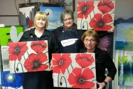 Students showing poppy paintings